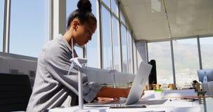 Zijaanzicht van Afrikaanse Amerikaanse Onderneemster die laptop met behulp van bij bureau in een modern bureau 4k stock video