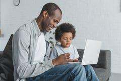 zijaanzicht van Afrikaanse Amerikaanse vader die op iets letten bij laptop met zoon stock afbeelding