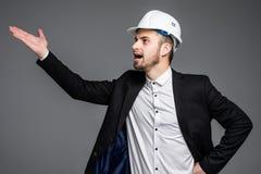 Zijaanzicht van architect die bouwvakker gillen dragen uit luid op grijze achtergrond met de ruimte van de exemplaartekst royalty-vrije stock fotografie