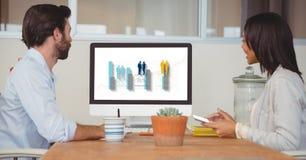 Zijaanzicht van bedrijfsmensen die grafiek op het computerscherm bekijken terwijl het zitten in bureau stock fotografie
