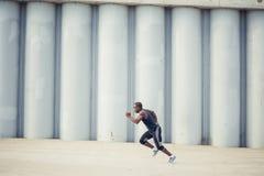 Zijaanzicht van besnoeiings het Zwarte atleet sprinten op de straat Royalty-vrije Stock Fotografie