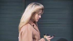 Zijaanzicht van blondevrouw met koffie die en Web het surfen lopen stock video