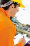 Zijaanzicht van bouwvakker het schrijven op klembord bij bouwwerf Royalty-vrije Stock Afbeeldingen