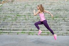 Zijaanzicht van de actieve sportieve jonge lopende atleet van de vrouwenagent met de fitness van de de sportgezondheid van het ex Stock Afbeeldingen