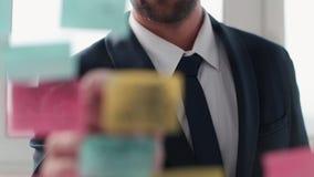 Zijaanzicht van de elegante mens wat betreft lippen en brainstorming op projectidee die stickers op glasraad bekijken stock video