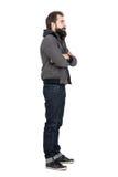 Zijaanzicht van de gebaarde mens die jasje over sweatshirt met een kap met gekruiste wapens dragen die weg eruit zien Stock Foto's