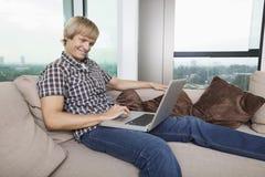 Zijaanzicht van de glimlachende medio-volwassen mens die laptop op bank thuis met behulp van Royalty-vrije Stock Foto's