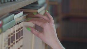 Zijaanzicht van de hand van de jonge student die met heldergroene manicure het boek in een bibliotheek dicht omhoog kiezen Het me stock footage