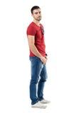 Zijaanzicht van de jonge ontspannen toevallige mens in rode t-shirt en jeans die camera bekijken stock foto's