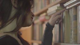 Zijaanzicht van de jonge student die het boek in een bibliotheek dicht omhoog kiezen Het meisje neemt oud boek van het boekenrek stock footage