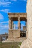 Zijaanzicht van de Portiek van de Kariatiden met een vogel die in een zeer blauwe hemel op de Erechtheion-tempel gewijd aan Athen royalty-vrije stock afbeeldingen