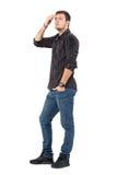 Zijaanzicht van de toevallige jonge mens in jeans en plaidoverhemd het aanpassen haar met hand die omhoog eruit zien royalty-vrije stock afbeelding