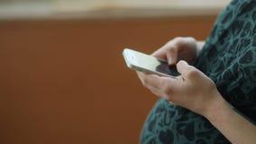 Zijaanzicht van de vrij zwangere vrouw in donkergroen retro noire uitstekend hof die haar smartphone gebruiken dichtbij houten ve stock video