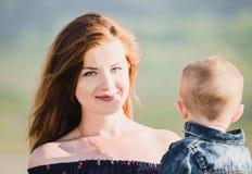 Zijaanzicht van de vrolijke mooie jonge baby van de vrouwenholding Royalty-vrije Stock Foto's