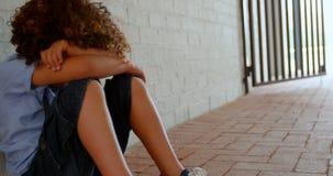 Zijaanzicht van de zitting van het mengen-rasschoolmeisje alleen op de vloer in gang op school 4k stock footage
