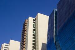 Zijaanzicht van een blauw gebogen modern collectief high-rise gebouw, en twee geelachtige bureaugebouwen Royalty-vrije Stock Foto