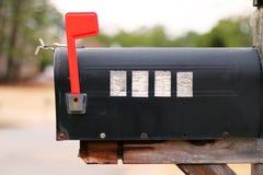 Zijaanzicht van een brievenbus met opgeheven vlag Stock Foto's