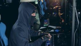 Zijaanzicht van een hakker die in vermomming met computers werkt stock footage
