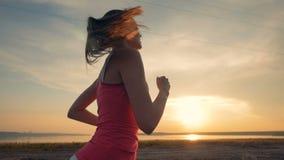 Zijaanzicht van een jonge aantrekkelijke vrouw die tijdens zonsondergang lopen Gezond levensstijlconcept stock footage