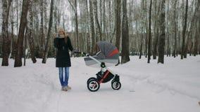 Zijaanzicht van een jonge moeder die met een babywandelwagen lopen stock footage