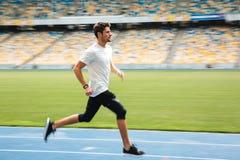 Zijaanzicht van een jonge sportman die op een renbaan lopen Stock Afbeeldingen