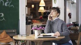 Zijaanzicht van een jonge vrouw die in een koffie bestuderen en op haar telefoon spreken stock videobeelden
