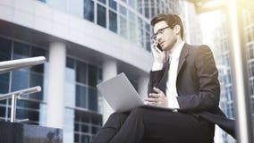 Zijaanzicht van een knappe jonge zakenman die met openlucht laptop zijn bureau werken Stock Foto's
