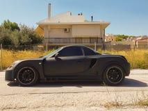Zijaanzicht van een luxe zwarte sportwagen Stock Afbeeldingen