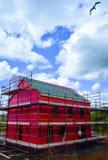 Zijaanzicht van een nieuw two-storey losgemaakt huis in aanbouw met rode beschermende laag en steiger stock afbeeldingen