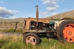 Zijaanzicht van een oude verlaten roestige landbouwtrekker in een gr. royalty-vrije stock afbeeldingen