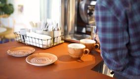 Zijaanzicht van een professionele barista die verse melk in de waterkruik bij de koffiewinkel, hete drankenvoorbereiding zetten A stock footage