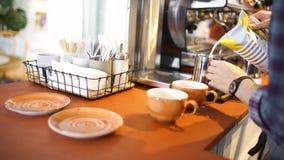 Zijaanzicht van een professionele barista die verse melk in de waterkruik bij de koffiewinkel, hete drankenvoorbereiding zetten A stock videobeelden