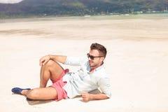 Zijaanzicht van een sexy mens die op het strand liggen Stock Foto's
