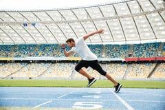 Zijaanzicht van een sportmens die op een renbaan lopen Royalty-vrije Stock Fotografie