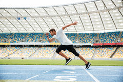 Zijaanzicht van een sportmens die op een renbaan lopen Royalty-vrije Stock Afbeeldingen