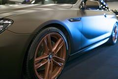 Zijaanzicht van een Stemmende coupé 2017 van BMW M6 in blauwe tonen Matte kleur Auto buitendetails stock afbeeldingen