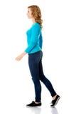 Zijaanzicht van een vrouw die langzaam lopen stock foto