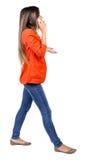 Zijaanzicht van een vrouw die met mobiele telefoon lopen Royalty-vrije Stock Afbeeldingen