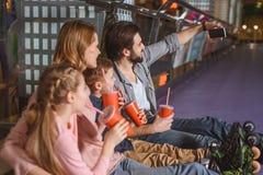 zijaanzicht van familie met dranken die selfie terwijl het rusten na het schaatsen nemen stock afbeelding