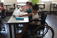 Zijaanzicht van gehandicapt schoolmeisje met klasgenoten die en bij bureau in klaslokaal bestuderen zitten stock afbeelding