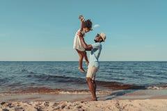zijaanzicht van gelukkige Afrikaanse Amerikaanse vader die met leuk weinig dochter spelen royalty-vrije stock foto