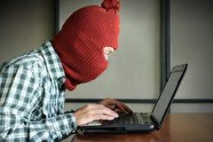 Zijaanzicht van gemaskeerde hakker die balaclava dragen die een laptop en gegeven van de diefstal belangrijk informatie kijken Ne stock fotografie
