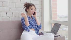 Zijaanzicht van glimlachende donkerbruine vrouw die in pyjama's op laag met laptop computer zitten terwijl thuis het spreken door stock footage