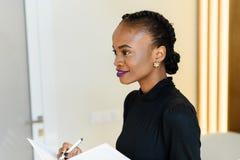 Zijaanzicht van glimlachende mooie bedrijfsvrouw die met heldere violette lippen witte blocnote en pen in licht bureau houden Stock Afbeelding
