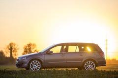 Zijaanzicht van grijze zilveren lege die auto in platteland op vaag landelijk landschap en heldere oranje duidelijke hemel bij zo stock fotografie