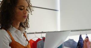 Zijaanzicht van het Afrikaanse Amerikaanse vrouwelijke blad van de de holdingsschets van de manierontwerper in workshop 4k stock footage