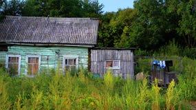Zijaanzicht van het blokhuis van het dorpslandbouwbedrijf en houten omheining, mening stock afbeelding