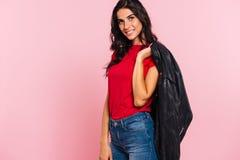 Zijaanzicht van het glimlachen van het donkerbruine jasje van de vrouwenholding op schouder Stock Foto's