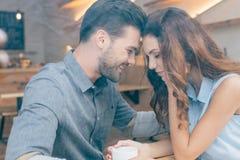 zijaanzicht van het glimlachen paarzitting bij lijst aangaande romantische datum stock foto