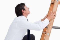 Zijaanzicht van het jonge kleinhandelaar beklimmen op een ladder Royalty-vrije Stock Fotografie
